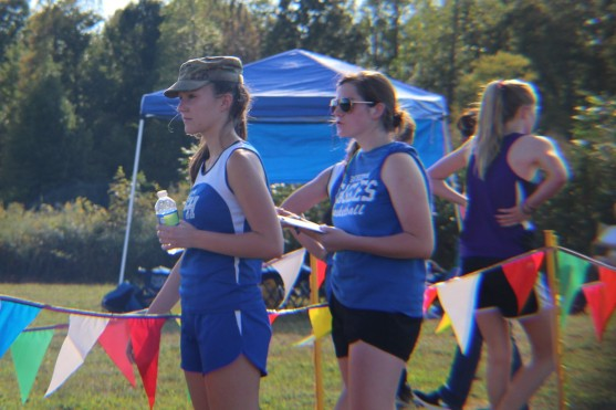 High school cross country runners Olivia Plunkett and Blair King wait at the finish line for the middle school girls to cross.